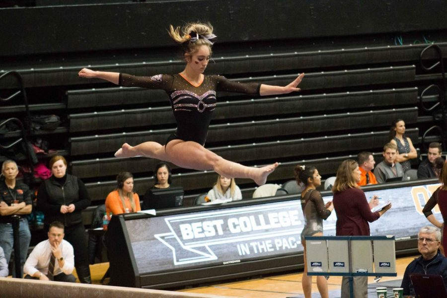 A junior and member of the OSU Gymnastics team, Dani Dessaints, performs on the beam.