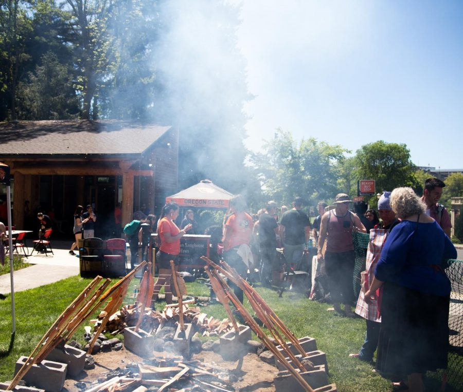 Attendees of the 19th Annual Salmon Bake gather around the fire where the salmon is prepared in the traditional way, served by the Longhouse on May 19. Those who waited in line were served salmon and multiple side dishes.