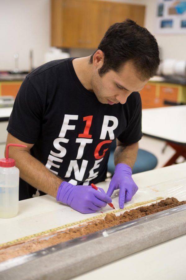 Adrian Gallo, a graduate student studying soil sciences, examines soil cores from various sites around the United States.