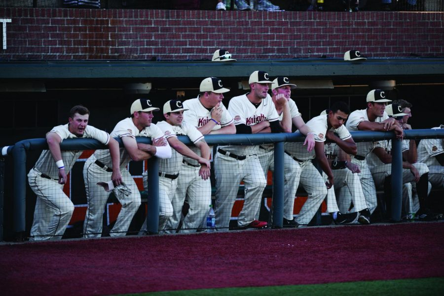 Corvallis Knights players watch their team compete against the Bellingham Bells from the dugout.