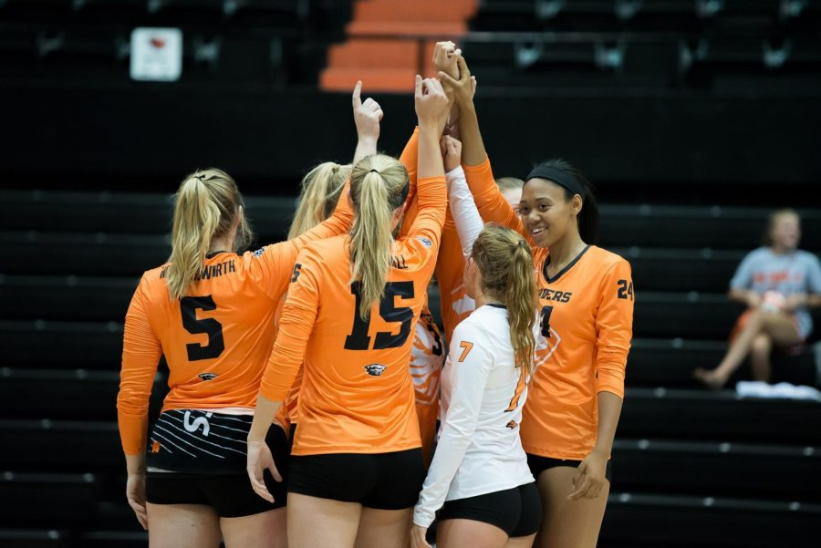Mary-Kate Marshall (second from the left), a fourth-year outside hitter on the OSU volleyball team, spikes the ball past two defenders in the Orange & Black OSU volleyball exhibition on August 18. Marshall was recently named to the preseason All-Pac-12 team.