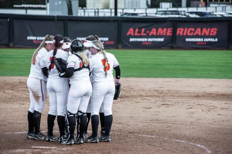 The softball team huddles on the eld. They are currently 20-14.