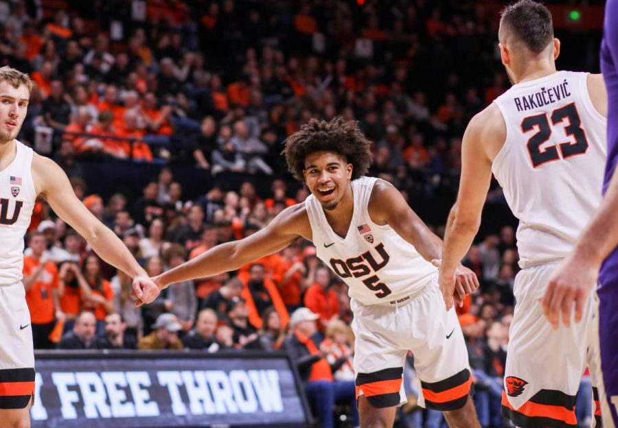 OSU sophomore guard Ethan Thompson gives his teammates Tres Tinkle (left) andGligorije Rakocevic (right) high fives in their game against Washington. Thompson,Gligorije and Tinkle were all selected for Pac-12 All-Academic awards on Tuesday.