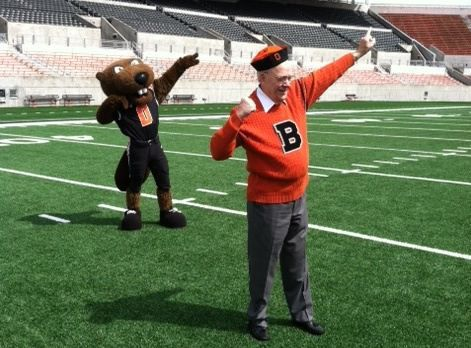 Ken Austin, the original Benny Beaver, poses with Benny Beaver on the field in Reser Stadium.