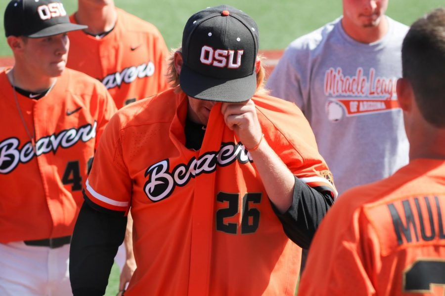 Oregon State senior right-handed pitcher Bryce Fehmel wipes his eyes with his uniform, the last time he will be able to do so.