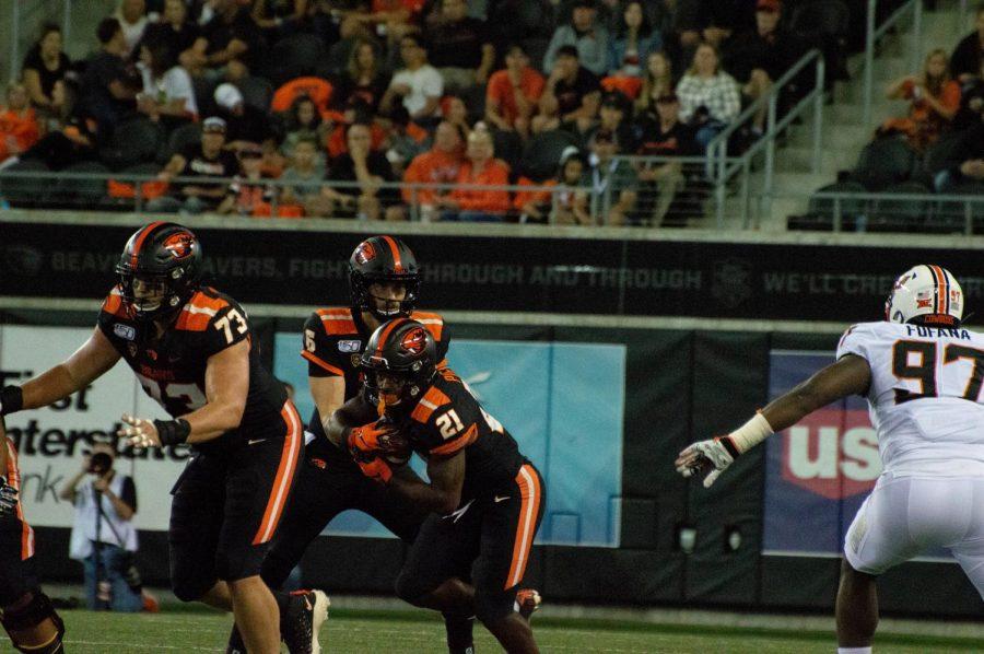 OSU+Football+redshirt+senior+quarterback+Jake+Luton+passes+off+the+ball+to+senior+running+back+Artavis+Pierce+versus+Oklahoma+State+at+Reser+Stadium+on+August+30.%C2%A0