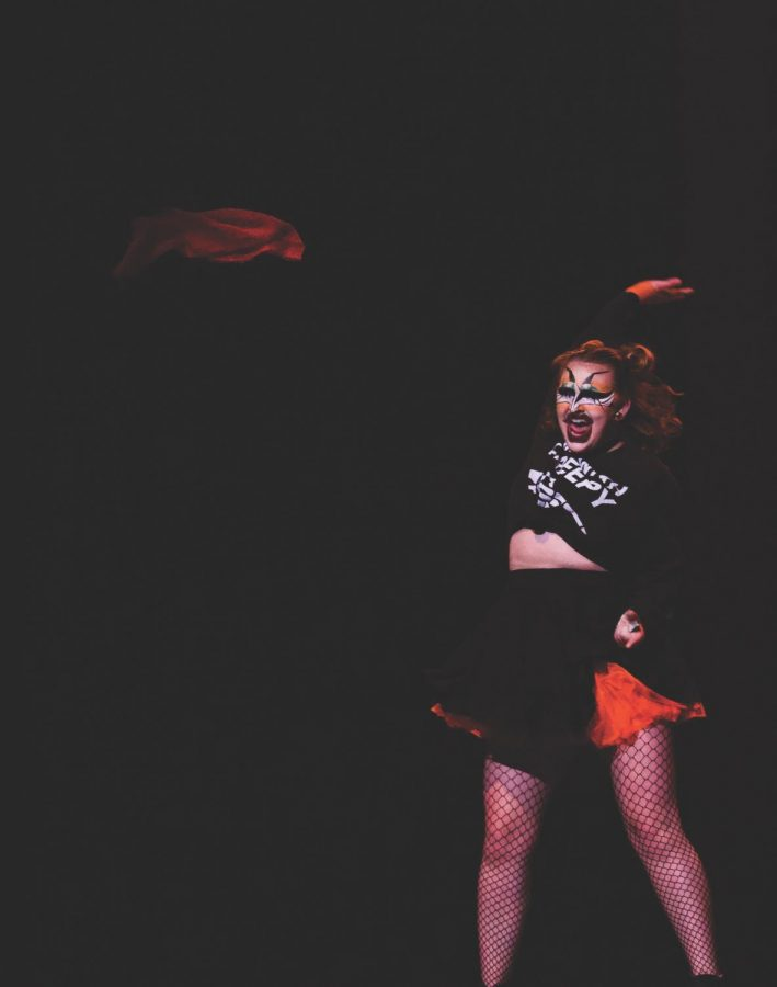 Drag+performer+Crusty+Kitty+pulls+a+red+cloth+from+their+skirt+as+they+perform+their+routine.%C2%A0