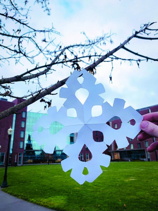 A paper snowflake, representing the upcoming holiday break, is held up in front of the International Living-Learning Center. Some international students will not be able to go home over winter break.