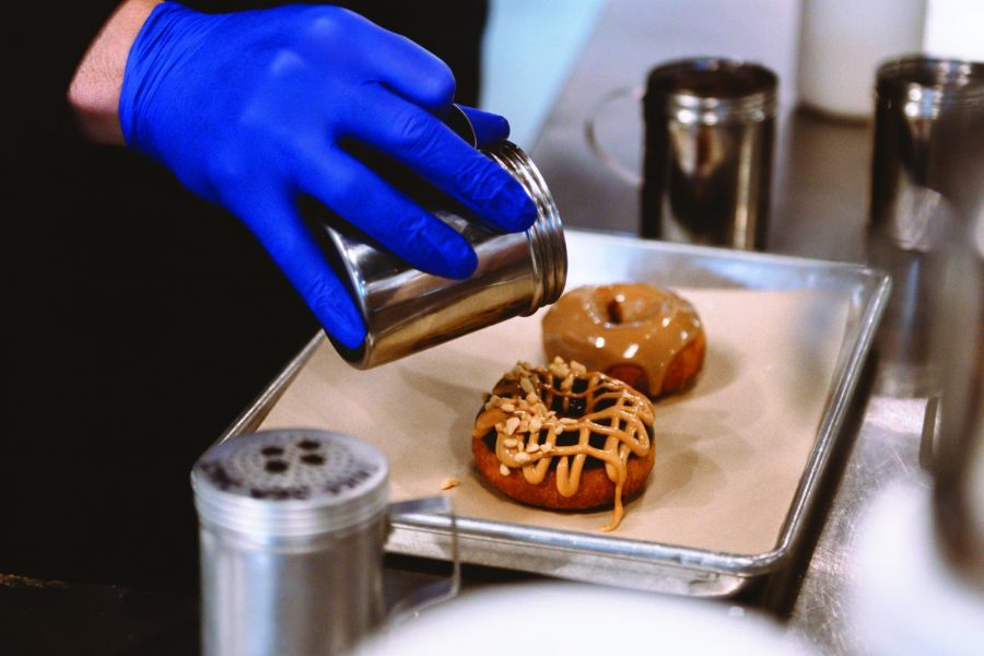 An+employee+finishes+off+decorating+a+customers+donut+order+at+Bennys+Donuts.+The+shop+offers+seasonal+flavors+and+options+that+cater+to+a+variety+of+dietary+restrictions.%C2%A0
