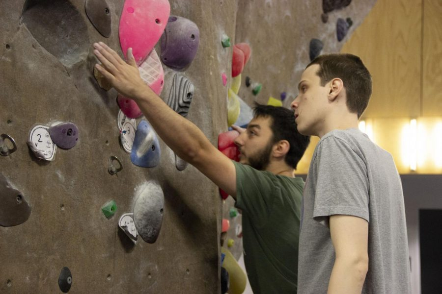 OSU student Luke Dowell shows Nick Boyce a way to scale a difficult route on the climbing wall at the McAlexander Fieldhouse.