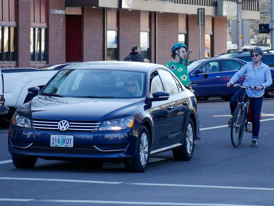 Two+cyclists+wait+behind+a+car+as+they+navigate+their+way+around+downtown+Corvallis.+The+Corvallis+City+Council+recently+voted+to+direct+funds+toward+future+safety+projects.