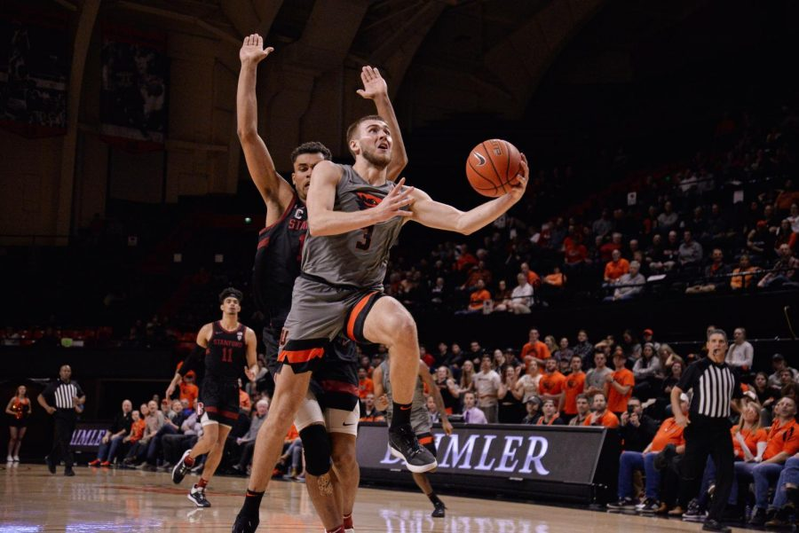OSU senior forward Tres Tinkle goes up for a shot against a Stanford defender in Gill Coliseum on March 5.