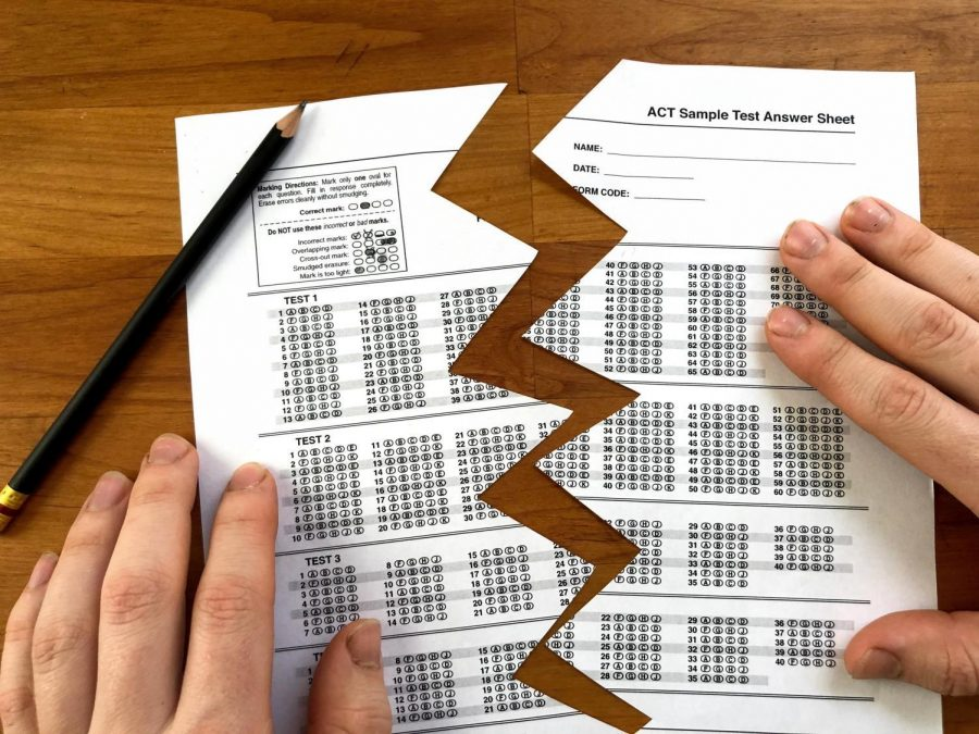 """Pictured is a photo illustration of a practice ACT test that is ripped down the center. President Ed Ray released a statement on March 25, notifying Oregon State University students that standardized testing scores—the ACT or SAT—would no longer be required for admission,allowing for a """"test-flexible"""" approach."""