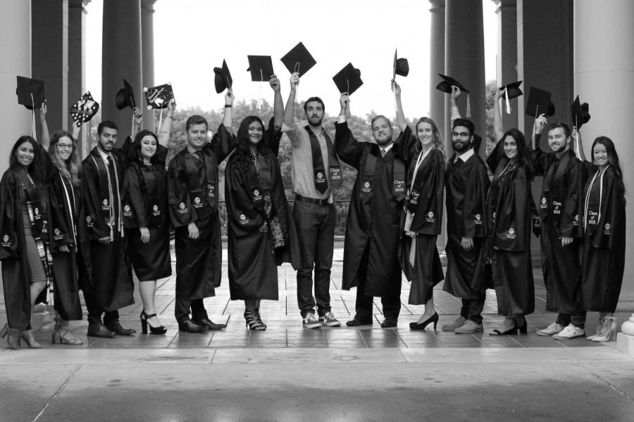 2018 Graduating students associated with DamDiverse pose under the Weatherford Hall arch for a photo.