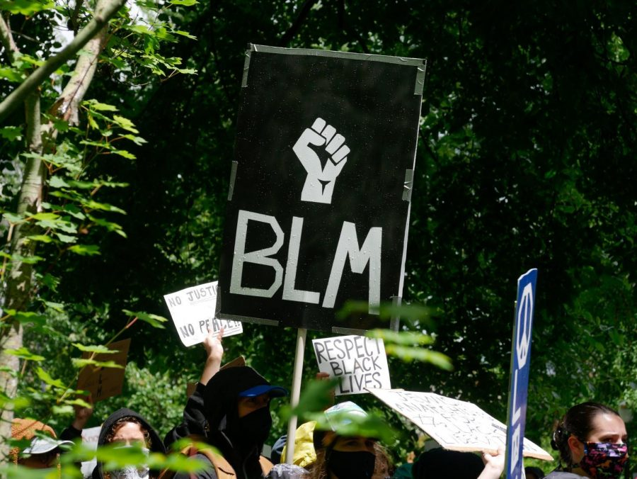 Face mask-wearing marchers hold signs and chant during the June 7 March for Black Lives.