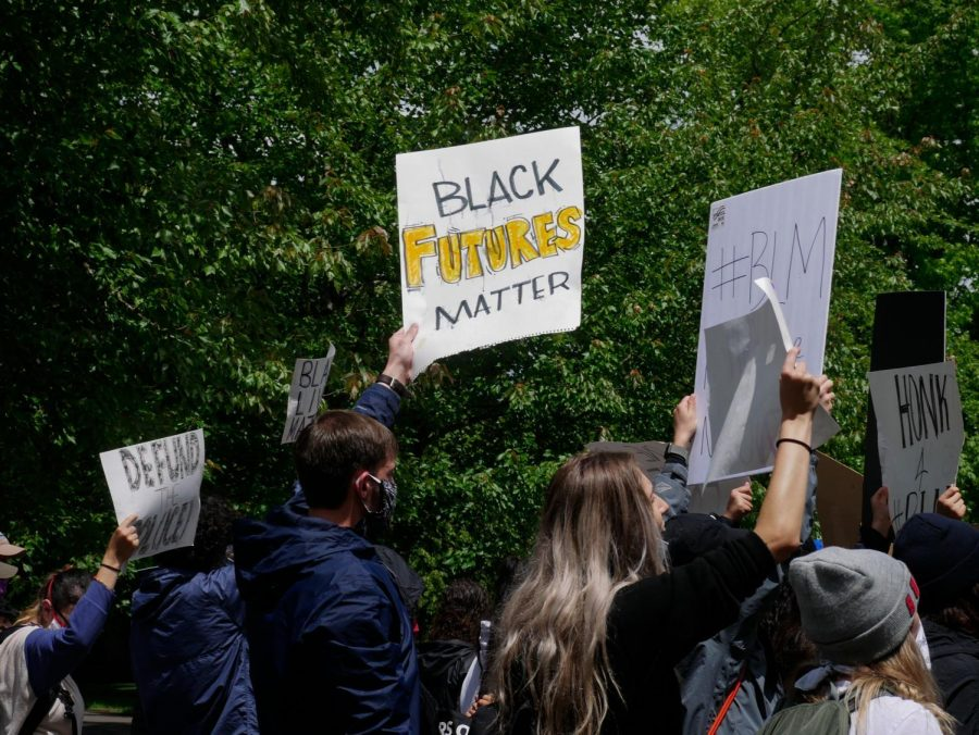 Face mask-wearing marchers hold signs and chant during the March for Black Lives on June 7.