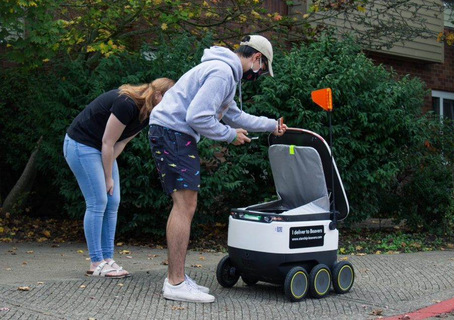 Third-year students Dominic Giuliano and Hailie Schweit grab their lunch from one of the Starship robots. These independent robots can bring food to residence halls for a contactless delivery.