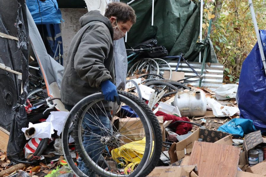 Merlin+can+be+seen+carrying+parts+to+his+recently-demolished+bike.+The+sporadic+theft%E2%80%94which+has+left+four+of+Merlins+camps+wasted%E2%80%94reminds+him+to+only+pack+the+bare+essentials+as+he+moves+on+to+a+new+outpost.