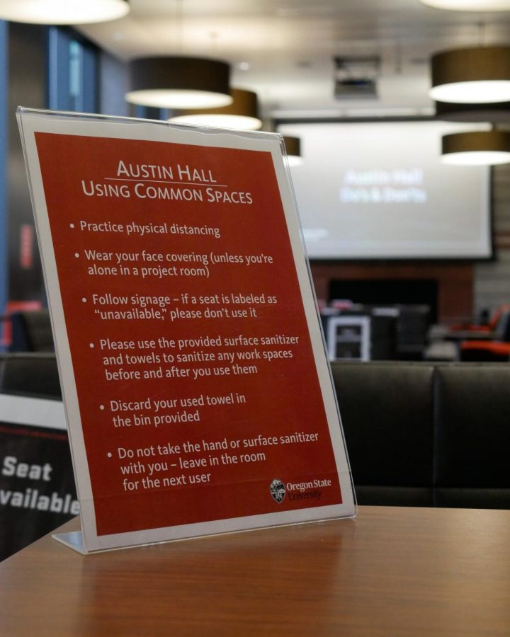 The signage in Austin Hall showing students how to socially distance while studying as a slideshow with their dos and don'ts plays in the background. Austin Hall has signs on each seat marking them as available or unavailable to show how students can socially distance.