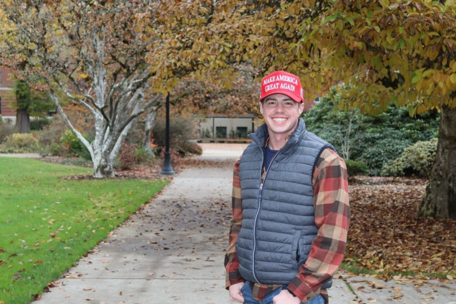 Member of College of Republicans Matthew Edwards is pictured outside of the Memorial Union. He can be seen smiling and proud to be American, no matter the stratification of American politics.