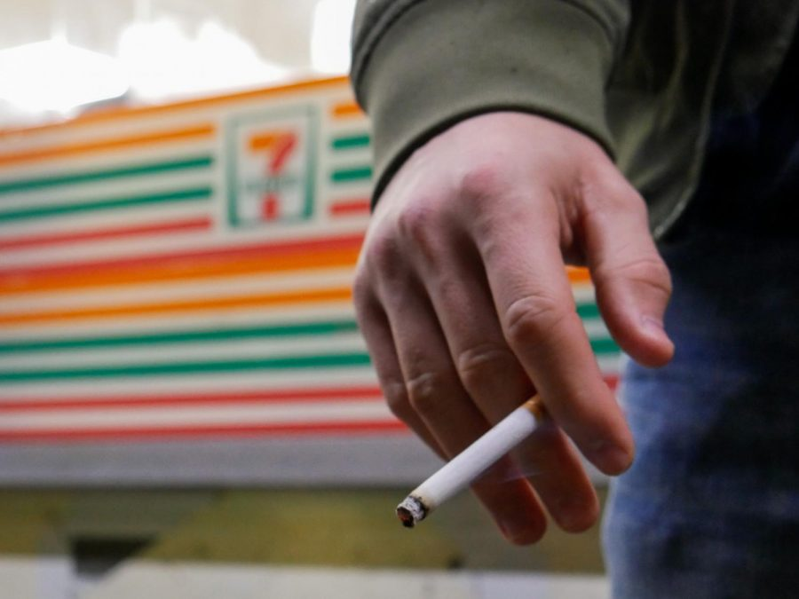 A+hand+holding+a+lit+cigarette+in+front+of+7+Eleven.+One+of+the+new+laws+in+Oregon+has+increased+the+tax+on+cigarettes+and+cigars+as+well+as+established+a+tax+on+e-cigarettes+and+vaping+products.