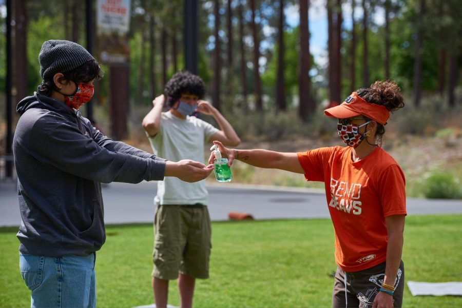 Members+of+the+OSU+community+share+hand+sanitizer+on+the+lawn+of+the+OSU+cascades+campus.%C2%A0