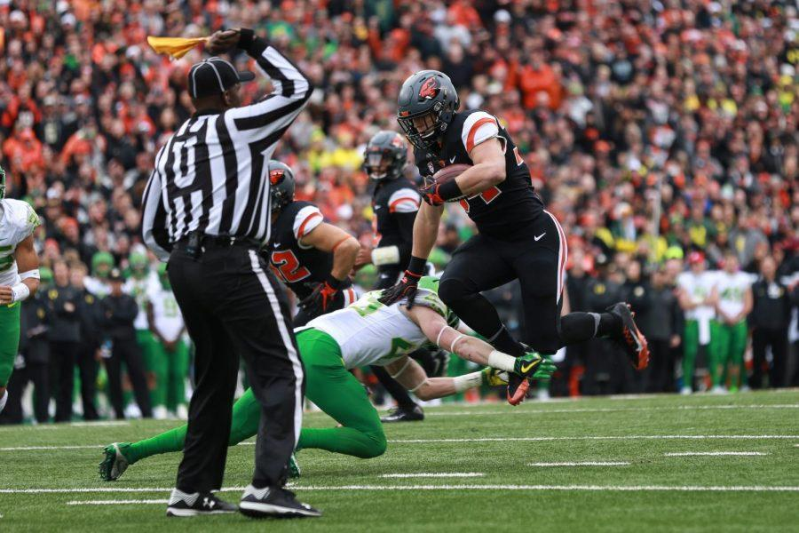 In this file photo from 2016, Oregon State sophomore running back Ryan Nall hurdles over an Oregon defender. Nall finished the game with four rushing touchdowns, helping propel the Beavers offense to a 34-24 win.