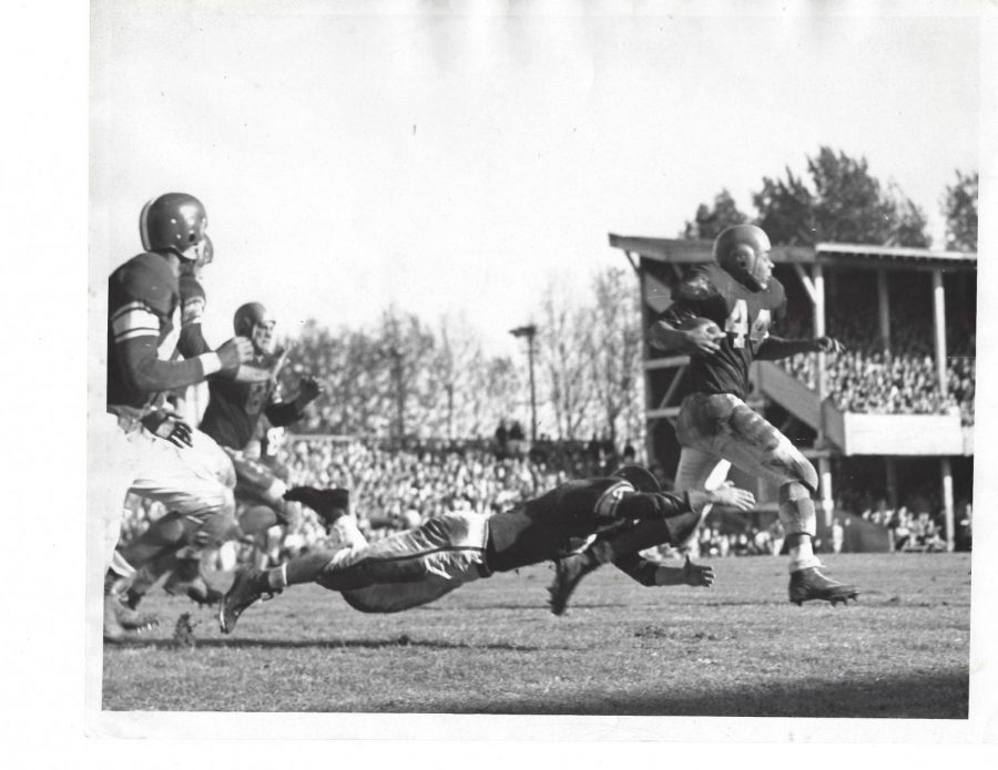 Oregon State punter and running back Dave Mann sprints away from a tackler. Mann played for the Beavers from 1951-1954, and was the first Black athlete to play for the Beavers football team.