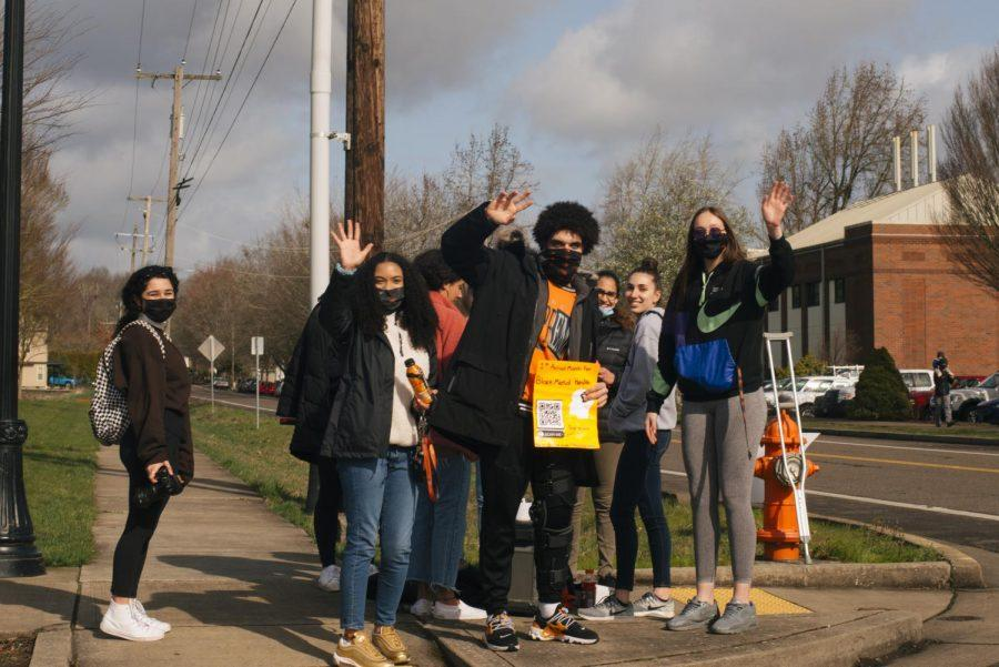 Organizers and participants wave to pedestrians and cars traveling through the intersection of Campus Way and NW 35th Street. On Feb. 27, its estimated over 40 people participated in person in the 1st Annual Black Mental Health March, organizers are already in talks for planning next years event.