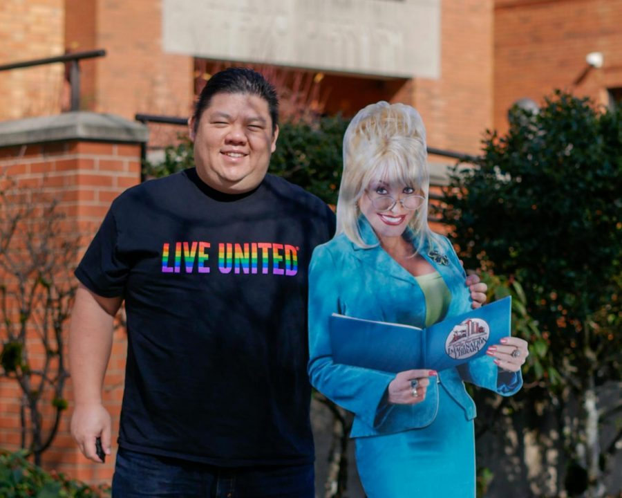President and CEO of United Way of Linn, Benton and Lincoln Counties, Blake Pang with a promotional cardboard cutout of Dolly Parton in front of the Corvallis Public Library. Corvallis Public Library has recently adopted Dolly Parton's Imagination Library program which mails local children books from when theyre born until they're 5 years old.
