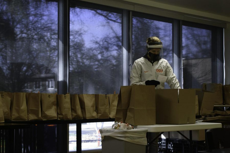 Member of the Human Service Resource Center Food Pantry Katlyn Varney prepares grocery bags for pickup on Feb. 17 at Champinefu Lodge on OSUs Corvallis campus. Due to the COVID-19 pandemic, food insecurity has risen among the Corvallis community.