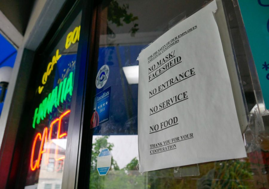 A sign detailing Local Boyz Cafe's current rules requiring a mask for service. Local businesses have had to be more direct with their signage since the CDC has announced that people who are vaccinated no longer need to wear masks inside or outside.