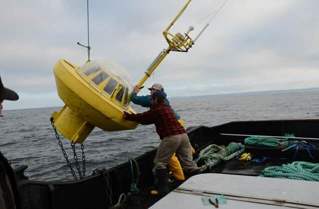 Researchers push out a measurement buoy onto the ocean currents. These buoys measure weather variables such as wave height that are considered in wave energy research facilities.