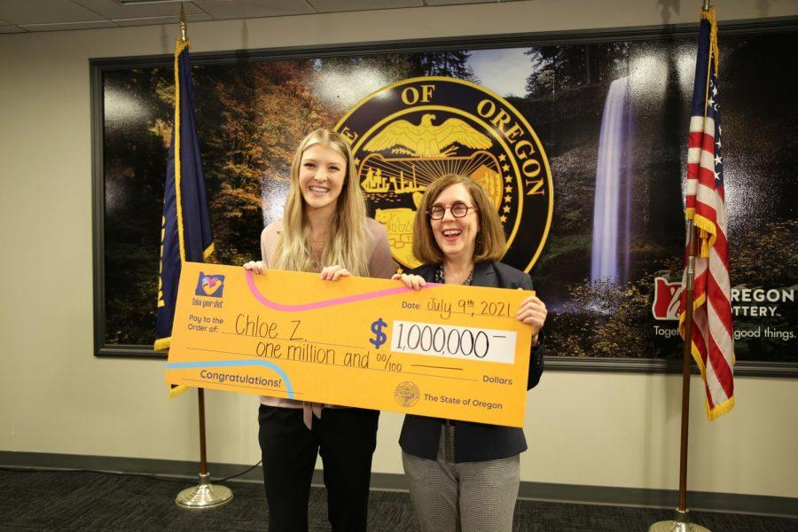 Oregon State University fourth-year fine arts student Chloe Zinda, left, and Oregon Governor Kate Brown hold an oversize check for $1 million, the grand prize for the Take Your Shot, Oregon campaign. Zinda plans to pay off school loans and invest the money into buying a house or art studio of her own.