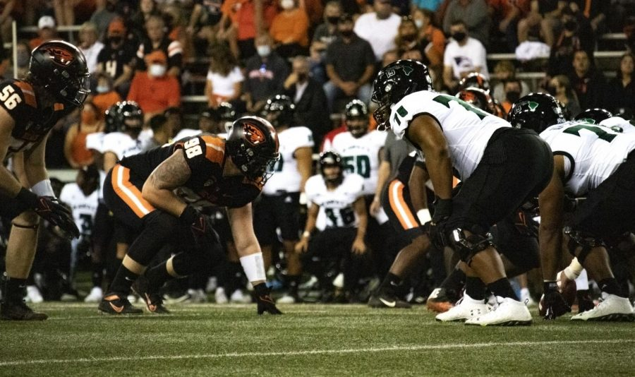 Redshirt-sophomore outside linebacker Riley Sharp (56) and redshirt-junior defensive lineman Cody Anderson (98) wait for the ball to be snapped to rush the quarterback.
