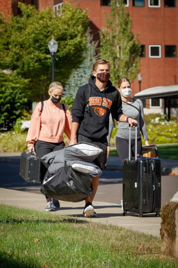 An incoming student carrying a suitcase and entering a dorm during Oregon State University's first day of move-in on Sept. 19. The incoming class will be the first group of freshman to experience in-person learning since OSU announced in-person plans for the 2021-22 academic year.