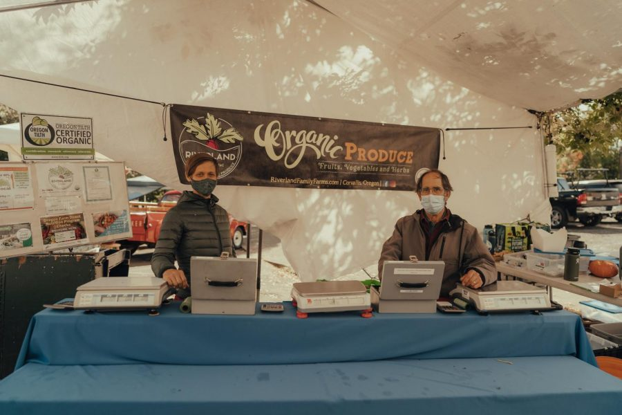 Owner of Riverland Family Farms Annaliese Watson (left), and manager Doug Eldon (right), pictured at their booth at the Corvallis Farmers Market located in downtown Corvallis, Ore. Eldon says their business has seen decreased sales since the beginning of the COVID-19 pandemic.