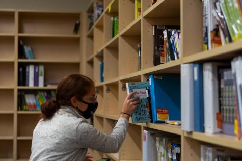 Preciosa Martinez, the graduate assistant of the Human Services Resource Center textbook lending program, retrieves a book from a shelf on Monday, Sept. 27th. The textbook lending program provides textbooks at no cost to students in need.